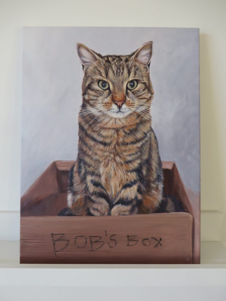acrylic painting of a tabby cat sitting in a cardboard box